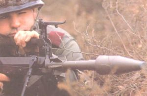 French soldier aims with the rifle grenade, mounted to the barrel of the FAMAS assault rifle.