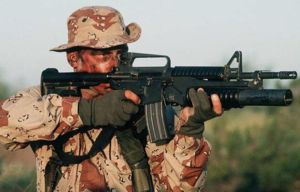 American soldier aims with the M4 carbine, combined with M203 underbarrel grenade launcher.