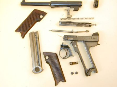Nambu Type 14 pistol, field stripped; note detached triggerguard and a separate locking member under the barrel.