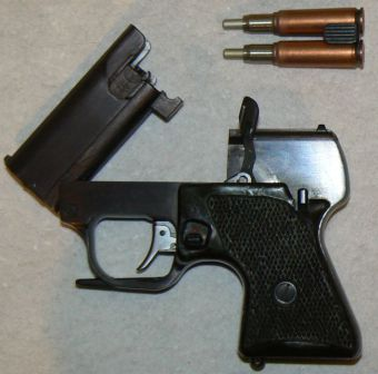 MSP pistol, left side. Barrel cluster is opened for reloading, and a clip with two fired SP-3 cases is shown