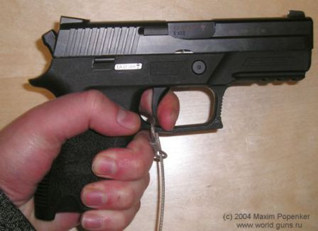 SIG-Sauer P250 DCc (compact) in the hand. Trigger is pulled partially, and the bobbed hammer is visible at the rear of the slide.