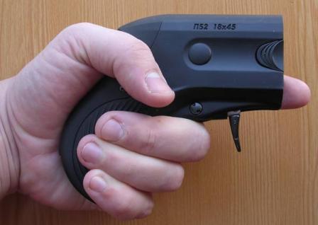 Бесствольный травматический пистолет Оса-Эгида ПБ-2 в положении готовности к стрельбе. Рука стрелка выжала клавишу предохранителя на рукоятке, спусковой крючок автоматически перешел в боевое положение