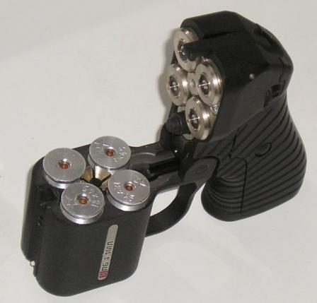 Пистолет травматический бесствольный Оса ПБ-4-1МЛ; блок стволов откинут для перезарядки. Хорошо видны центральный экстрактор с каналом по оси для прохождения луча ЛЦУ и спусковые контакты на колодке оружия.