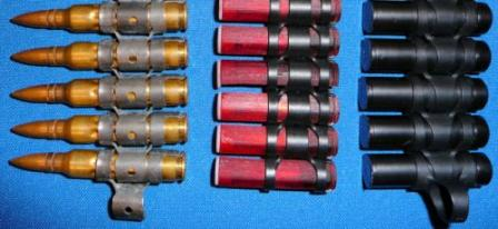 LSAT machine gun ammunition in belt links: caseless in the middle and cased telescoped right, compared to the standard 5.56x45 NATO at left.