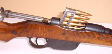 Steyr Mannlicher M95/30 rifle, with bolt open and loaded clip partially inserted into action; note how the bolt handle remains horizontal, as opposed to more common rotating bolt actions such as Mauser.
