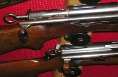 View on K31 bolt and receiver; top rifle has the bolt partially retracted; the curved track on the bolt body and stud on charging handle are clearly visible.