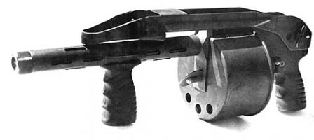 The original Striker shotgun with 12 inches barrel. Note the winding key at the front of the cylinder / magazine, and the top-folding butt (folded).