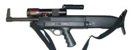 The HS model 10B shotgun with the flashlight attached and carrying handle raised.