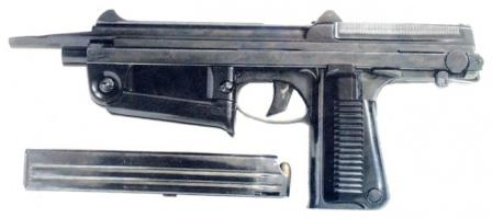 PM-63 submachine gun with front grip and buttstock folded; 25-round magazine is removed from grip.