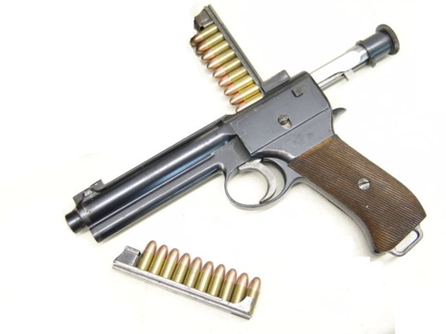 Roth M.7 (model 1907) self-loading pistol; bolt is locked back, and a loaded clip is inserted into the gun, ready to load the magazine.