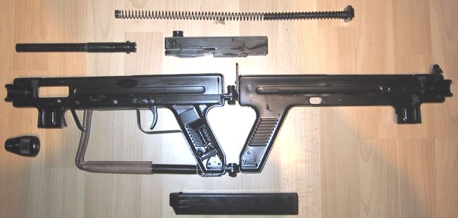 Madsen model 1950 submachine gun, completely disassembled. Note the magazine loading tool stored inside the hollow pistol grip.