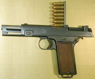 Steyr Hahn M1911 self-loading pistol, with clip inserted and cartridges ready to be pushed into the magazine.