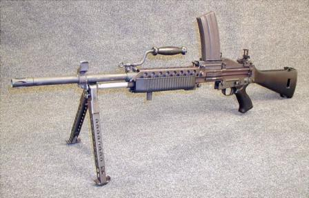Stoner 63A weapon in magazine-fed light machine gun configuration, with longer and heavier barrel. Note that sights are offset to the left because of overhead magazine.