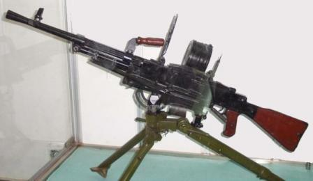 Type 67 machine gun on tripod, with 100-round drum belt container attached to the right side of receiver.