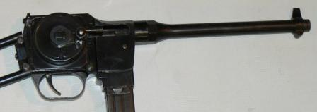 Close-up view on receiver ofMGD PM-9, with rotating charging handle and folding magazinehousing.