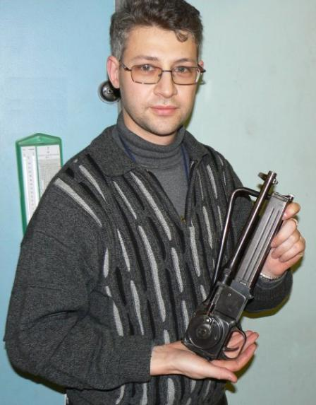 Authordemonstrates the compact size of MGD PM-9 submachine gun in foldedconfiguration.