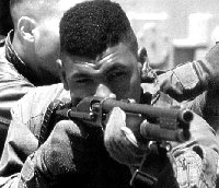 US marine aiming with the Remington 870 pump-action shotgun