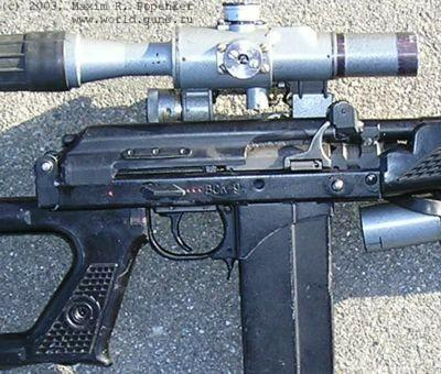 Close-up view on the receiver and controls of VSK-94. Note the safety/fireselector switch above the trigger which allows for semiautomatic and fullautomatic fire, and a folding charging handle.